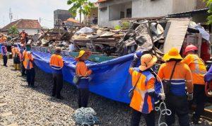 Pegawai PT KAI Daop 8 Surabaya mengangkut sampah keatas kereta yang telah disiapkan dalam giat kerja bakti bersama masyarakat.