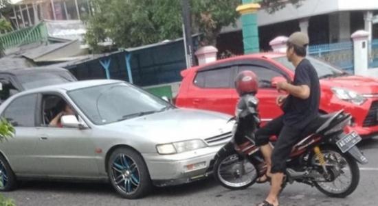 Pengendara sepeda motor dengan santay menghadang mobil