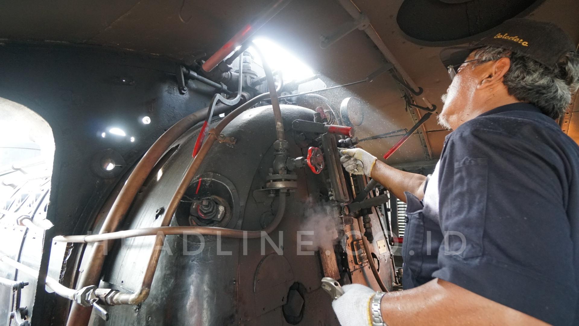 Suharyanto Kepala Restorasi Lokomotif Uap D1410 sedang melakukan pengecekan terakhir sebelum keberangkatannya menuju Stasiun Purwosari.