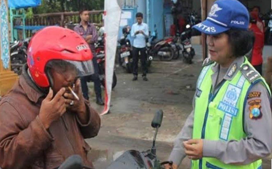 Salah satu pengendara yang merokok saat berkendara dikenakan sanksi oleh Polisi