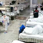 Petugas medis dengan pakaian pelindung merawat pasien di Pusat Konferensi dan Pameran Internasional Wuhan, yang diubah menjadi rumah sakit sementara.