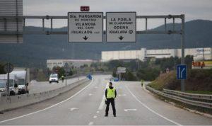 Seorang polisi Spanyol berdiri di tengah ruas jalan dekat kota Igualada yang di-lockdown karena wabah virus Corona (Foto: Joan Mateu)