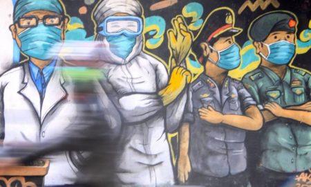 Pengendara melintas di depan mural tentang pandemi COVID-19 di Kawasan Bangil, Pasuruan, Sidoarjo, Jawa Timur. (Foto: ANTARA FOTO Umarul Faruq)