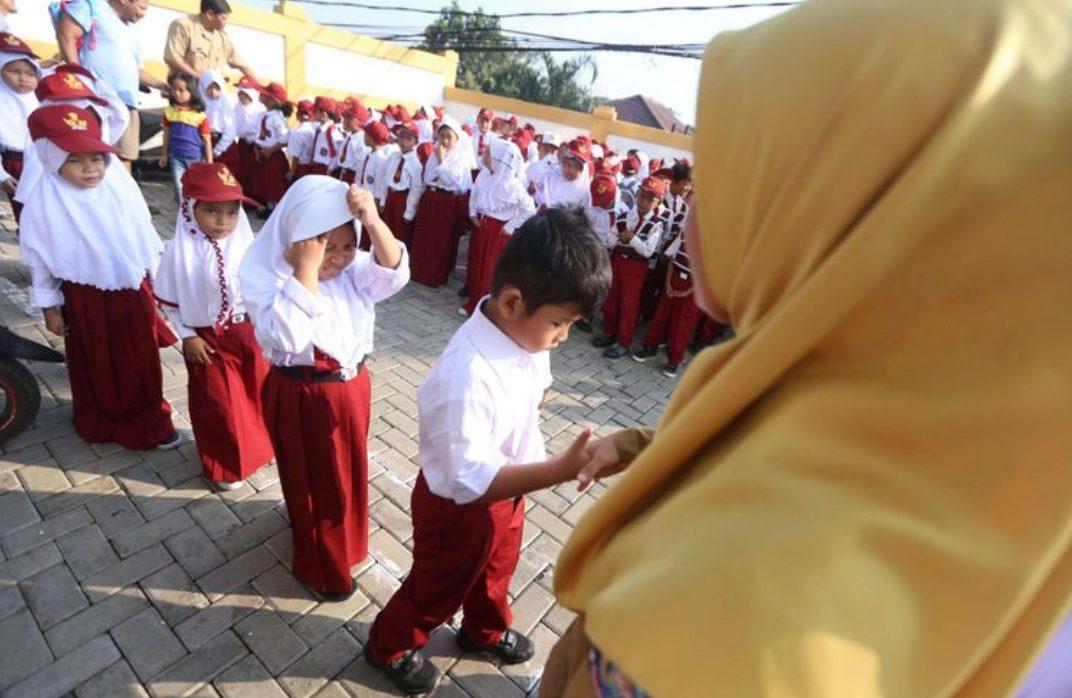 Guru bersalaman dengan murid baru kelas 1 saat hari pertama masuk sekolah, di SD Negeri Lengkong Wetan 1, Serpong Utara, Tangerang Selatan. (Foto: Kompas.com)
