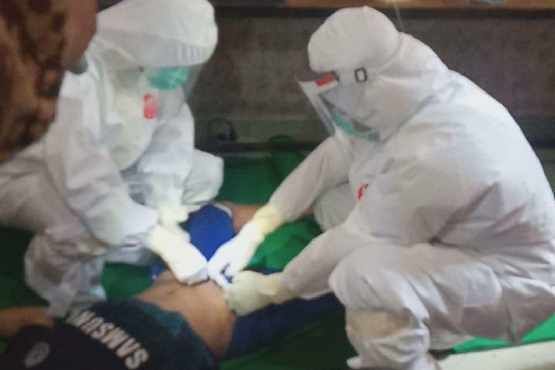Terlihat petugas medis memakai APD memeriksa mayat pemuda yang ditemukan didalam kamarnya. (Foto: Istimewa)
