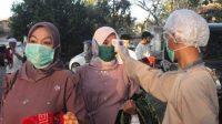 Tim kesehatan memeriksa suhu tubuh peserta salat Idulfitri yang masuk ke lapangan Prawatasari , Cianjur, Jawa Barat. (Foto: Tribunjabar)