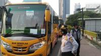 Petugas Dinas Perhubungan DKI Jakarta menyediakan bus sekolah untuk mengangkut penumpang KRL gang terlantar di Jakarta menuju daerah tujuan di Bodetabek