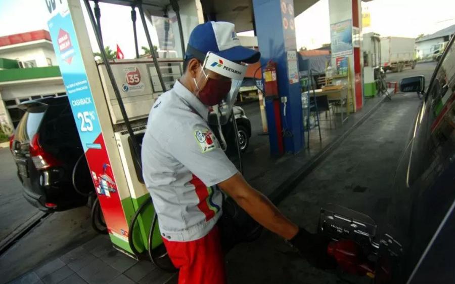 Petugas menggunakan pelindung wajah saat mengisi bahan bakar minyak sebuah kendaraan di SPBU